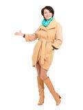 Frau im beige Mantel mit grünem Schal zeigend auf etwas Lizenzfreies Stockfoto
