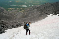Frau im Berg, der auf Schnee steht Stockfotografie