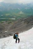 Frau im Berg, der auf Schnee steht Lizenzfreies Stockfoto