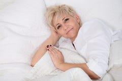 Frau im Bett lizenzfreie stockfotos