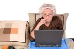 Frau im Bett, arbeitend Lizenzfreies Stockfoto