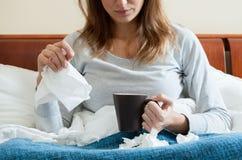 Frau im Bett, das eine Kälte hat Stockfotos