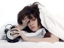 Frau im Bett, das müde Holdingalarmuhr weckt Stockfotos