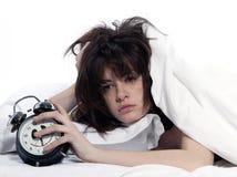 Frau im Bett, das müde Holdingalarmuhr weckt Stockbild