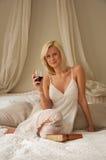 Frau im Bett, das mit Wein sich entspannt. Lizenzfreies Stockbild
