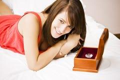 Frau im Bett ein Geschenk genießend Stockbild