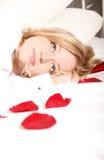Frau im Bett mit den Rosen-Blumenblättern Lizenzfreies Stockbild