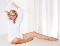 Frau im Bett mit einem großen Kissen Stockbilder
