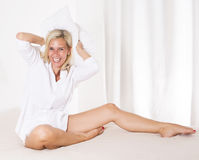 Frau im Bett mit einem großen Kissen Lizenzfreie Stockbilder