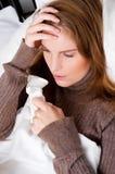 Frau im Bett mit einem Taschentuch Stockfoto