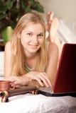 Frau im Bett mit Laptop Stockfoto