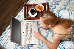 Frau im Bett mit Laptop Lizenzfreie Stockbilder
