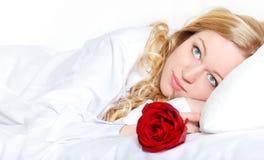 Frau im Bett mit Rose Lizenzfreie Stockbilder