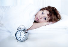 Frau im Bett mit Schlaflosigkeit, die nicht mit Wecker schlafen kann Stockfotos