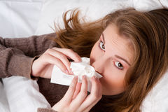 Frau im Bett mit Taschentuch Stockfotos