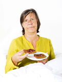 Frau im Bett mit Toast Stockbild