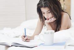 Frau im Bettschreiben auf einem Notizbuch Stockfotos