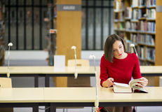 Frau im Bibliothekssuchvorgangwissen vom Buch Lizenzfreies Stockbild