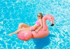 Frau im Bikini auf der aufblasbaren Matratze im Swimmingpool stockfotos