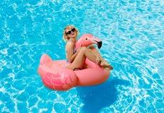 Frau im Bikini auf der aufblasbaren Matratze im Swimmingpool lizenzfreie stockbilder
