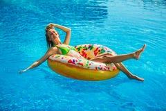 Frau im Bikini auf der aufblasbaren Matratze im Swimmingpool stockfoto