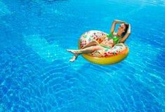Frau im Bikini auf der aufblasbaren Matratze im Swimmingpool stockbilder
