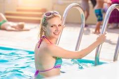 Frau im Bikini, der auf der Pooltreppe steht lizenzfreies stockbild