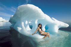 Frau im Bikini, der auf Eisberg sitzt stockbild