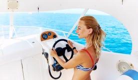 Frau im Bikini, der das Boot steuert Lizenzfreie Stockfotos