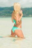 Frau im Bikini, der ihren BH beim Sitzen auf ihren Knien im wat repariert Lizenzfreies Stockbild