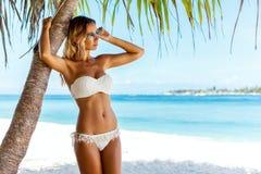 Frau im Bikini, der am Strand aufwirft Stockfotografie