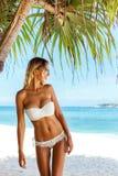 Frau im Bikini, der am Strand aufwirft Stockfoto