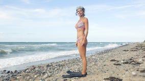 Frau im Bikini, der am Strand mit Schwimmenschutzbrillen steht Stockfotos
