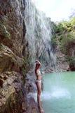 Frau im Bikini, der unter Wasserfall steht Lizenzfreies Stockfoto