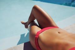 Frau im Bikini ein Sonnenbad nehmend durch den Poolside Stockfotografie