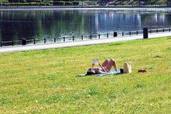 Frau im Bikini ein Sonnenbad nehmend durch den Teich, liegend auf Gras, Lesepapierbuch lizenzfreies stockfoto