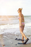 Frau im Bikini mit Flippern und Schutzbrillen auf dem Strand Stockfoto