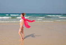 Frau im Bikini und im roten Schal gehend auf einen Strand Stockbilder