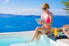 Frau im Bikini unter Verwendung der Tablette durch den Swimmingpool stockfotos