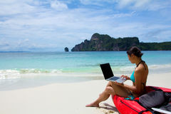 Frau im Bikini unter Verwendung des Laptops am Strand Stockbild