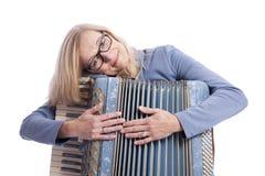 Frau im Blau mit Gläsern hält accordeon und lächelt Lizenzfreies Stockfoto