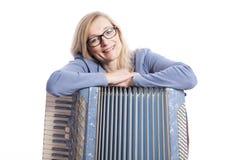 Frau im Blau mit Gläsern lehnt sich auf accordeon und lächelt Stockfoto