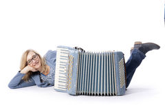 Frau im Blau mit Gläsern liegt hinter accordeon und lächelt Lizenzfreie Stockfotos