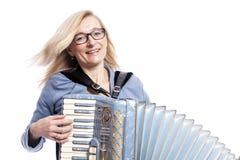 Frau im Blau mit Gläsern spielt accordeon und lächelt Lizenzfreie Stockfotos