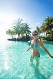 Frau im blauen Bikini innerhalb des tropischen Unbegrenztheitspools lizenzfreie stockbilder
