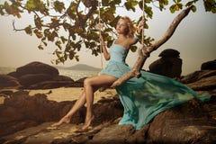 Frau im blauen flatternden Kleid, das auf einem Strand Swi schwingt Stockfotografie