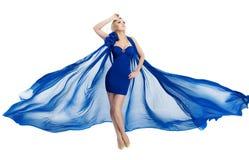 Frau im blauen flatternden Kleid, das auf Wind über Weiß wellenartig bewegt lizenzfreie stockfotos