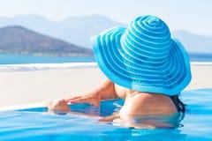 Frau im blauen Hut am Swimmingpool Lizenzfreie Stockbilder