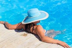 Frau im blauen Hut am Swimmingpool Stockbild