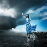 Frau im blauen Kleid, das für das Licht erreicht Stockfotos